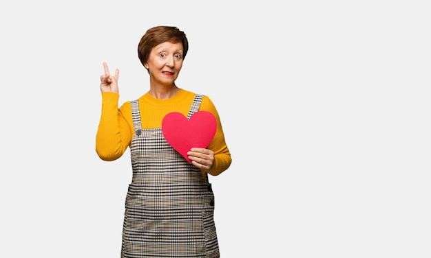 Middle aged woman celebrating valentines day fun and happy doing a gesture of victory