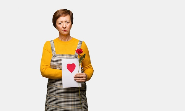 Middle aged woman celebrating valentines day looking straight ahead