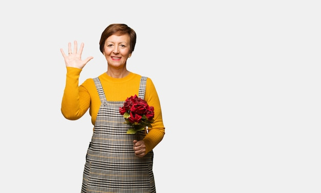 Middle aged woman celebrating valentines day showing number five