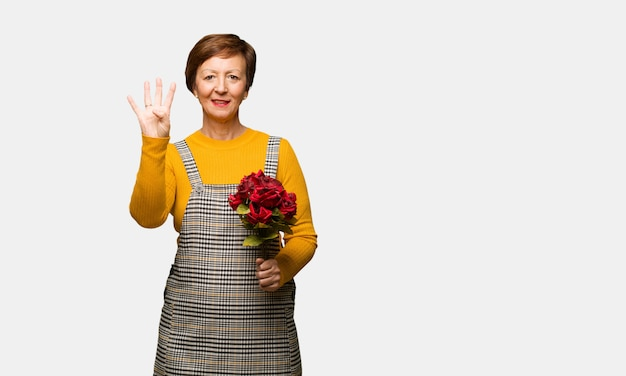 Middle aged woman celebrating valentines day showing number four