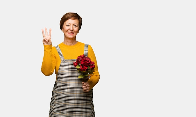 Middle aged woman celebrating valentines day showing number three