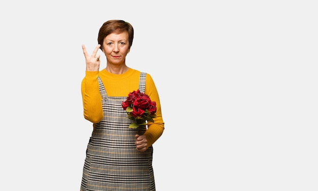 Middle aged woman celebrating valentines day showing number two