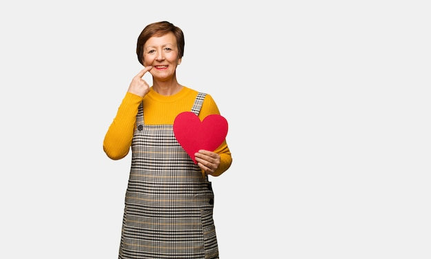 Middle aged woman celebrating valentines day smiles, pointing mouth