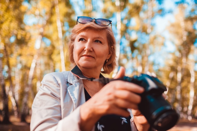 Middle aged woman checking images on camera in autumn forest