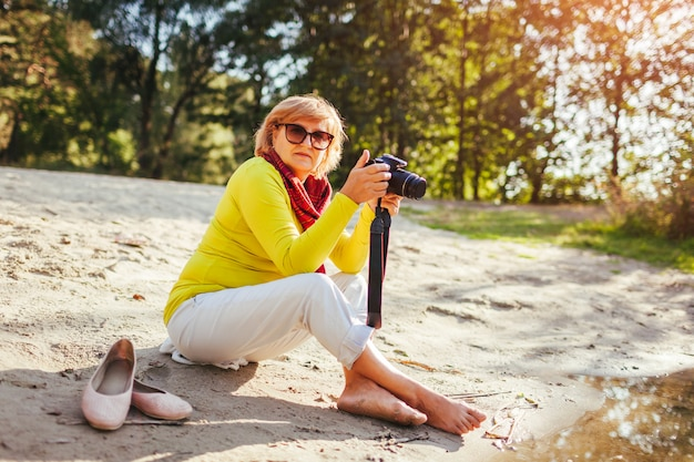 Middle aged woman checking images on camera sitting by autumn river bank