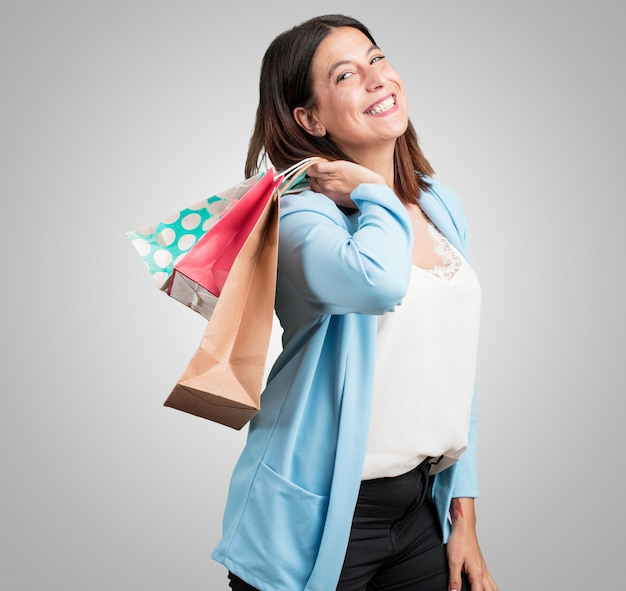 Middle aged woman cheerful and smiling, very excited carrying a shopping bags, ready to go shopping and look for new offers