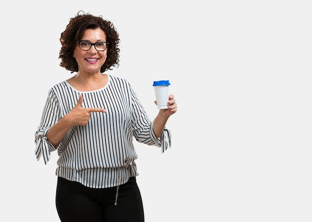 Middle aged woman cheerful and vital, holding a coffee to go, take away beverage