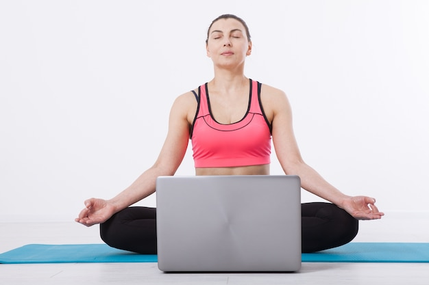 A middle-aged woman conducts yoga training using a laptop and internet communication