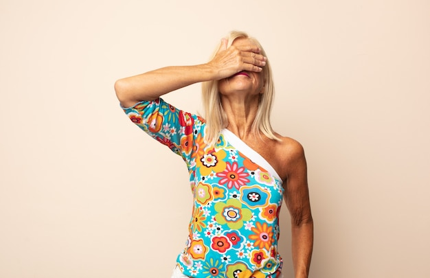 Женщина средних лет закрывает глаза одной рукой, чувствуя испуг или тревогу, недоумевая или слепо ожидая сюрприза