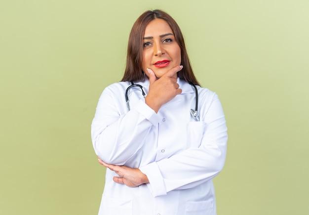 녹색 벽 위에 서서 생각하는 턱에 손을 대고 앞을 바라보는 청진기가 있는 흰색 코트를 입은 중년 여성 의사