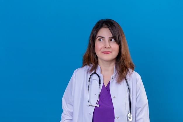 中年の女性医師が白いコートを着て、青い背景の上にずる賢く立って笑って聴診器でよそ見