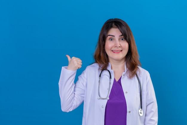 中年の女性医師が白いコートを着て、青い背景の上に立って親指で側を明るく指している笑顔のカメラを見て聴診器で