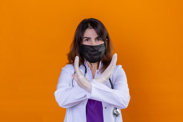 Middle aged woman doctor wearing white coat in black protective facial mask and with stethoscope crossing her hands shows gesture stop standing over isolated orange background