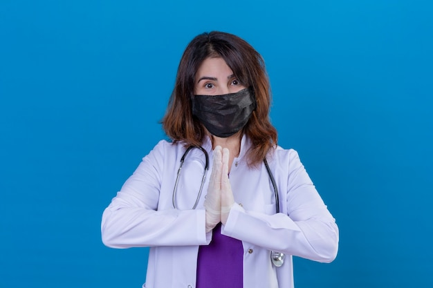 Middle aged woman doctor wearing white coat in black protective facial mask and with stethoscope holding hands in prayer namaste gesture feeling thankful and happy over isolated blue backgroun