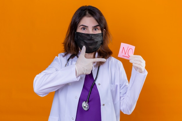 Middle aged woman doctor wearing white coat in black protective facial mask and with stethoscope holding reminder paper with no word pointing with finger to it over isolated orange background
