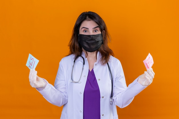 Middle aged woman doctor wearing white coat in black protective facial mask and with stethoscope holding reminder papers with yes and no words looking at camera surprised standing over orange