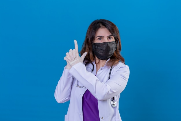 Middle aged woman doctor wearing white coat in black protective facial mask and with stethoscope holding symbolic gun with hand gesture playing killing shooting weapons angry face standing ov