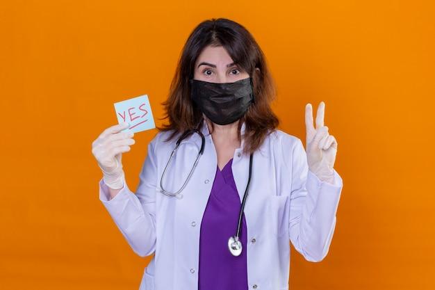 オレンジ色の背景に勝利のサインを示すはい単語でリマインダー紙を保持している聴診器で黒い防護マスクに白いコートを着ている中年の女性医師