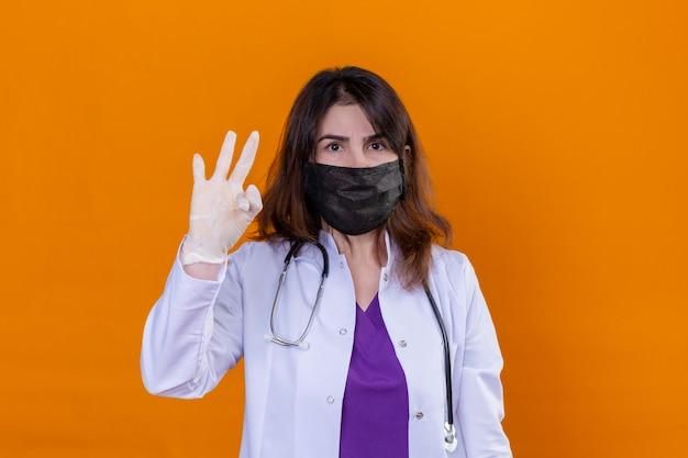 中年の女性医師が黒い保護マスクと白い背景の上にオレンジ色の背景の上に立ってokの標識をやっている自信のある表情でカメラを見て聴診器で白いコートを着ています。