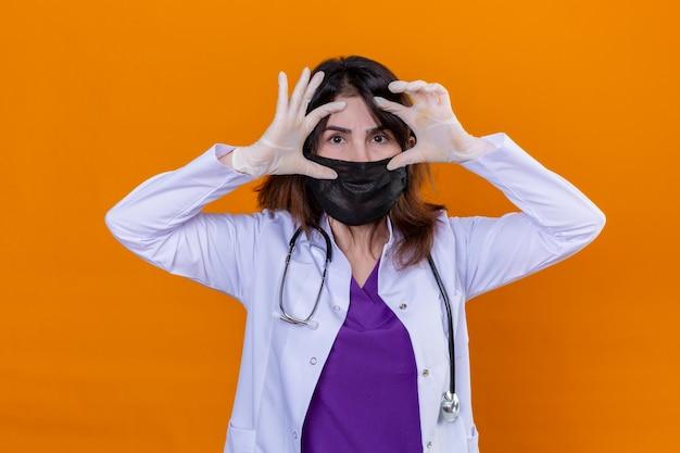中年の女性医師が黒い保護マスクと白い聴診器で白いコートを着て、眠っている指で目を開けようとして、孤立したあなたの上に立って朝の疲労のために疲れています。