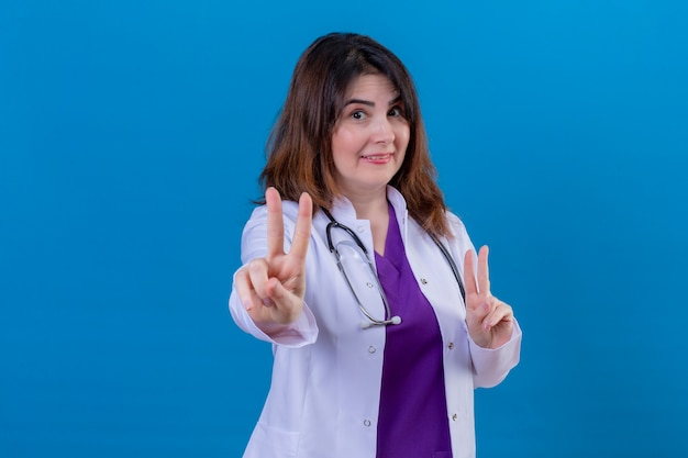 Middle aged woman doctor wearing white coat and with stethoscope looking at camera smiling cheerfully doing victory sign with both hands standing over blue background