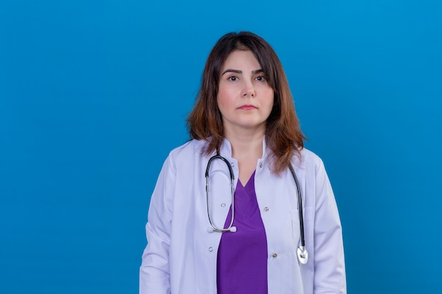 Middle aged woman doctor wearing white coat and with stethoscope looking at camera with serious confident expression standing over isolated blue background