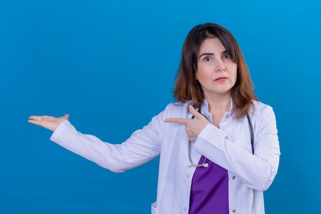 Middle aged woman doctor wearing white coat and with stethoscope looking confused pointing with both hands and finger to the side standing over blue background