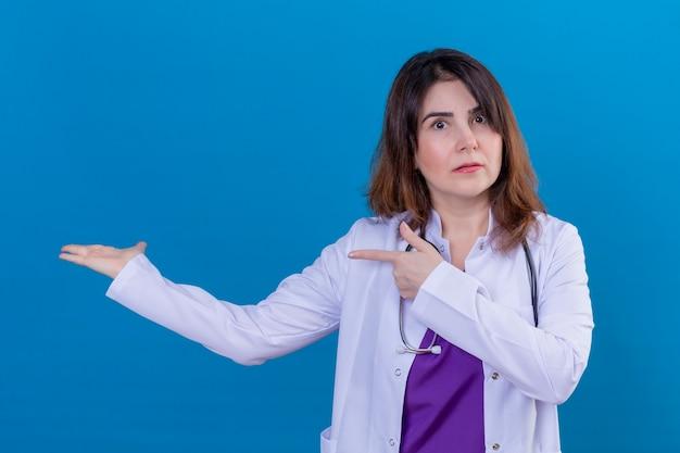 Donna di mezza età medico indossa camice bianco e con uno stetoscopio cercando confuso puntando con entrambe le mani e il dito a lato in piedi su sfondo blu