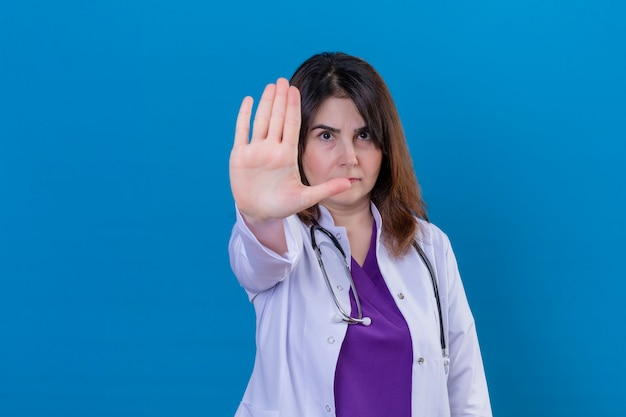 Middle aged woman doctor wearing white coat and with stethoscope standing with open hand doing stop sign with serious and confident expression defense gesture over blue background
