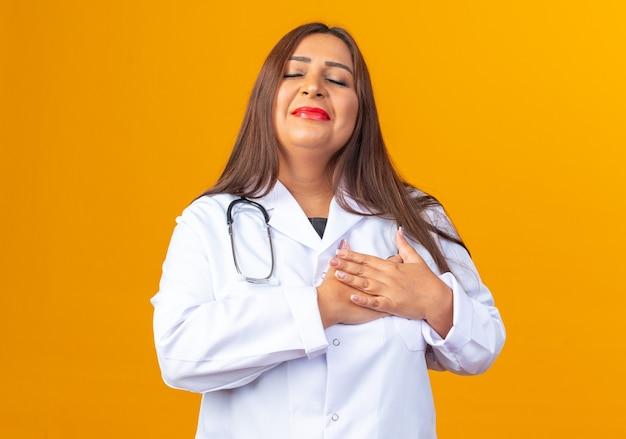 Medico donna di mezza età in camice bianco con stetoscopio che si tiene per mano sul petto provando emozioni positive in piedi sul muro arancione