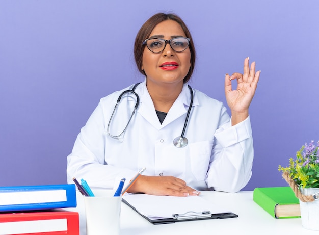 Middle aged woman doctor in white coat with stethoscope wearing glasses looking at front smiling confident doing ok sign sitting at the table over blue wall