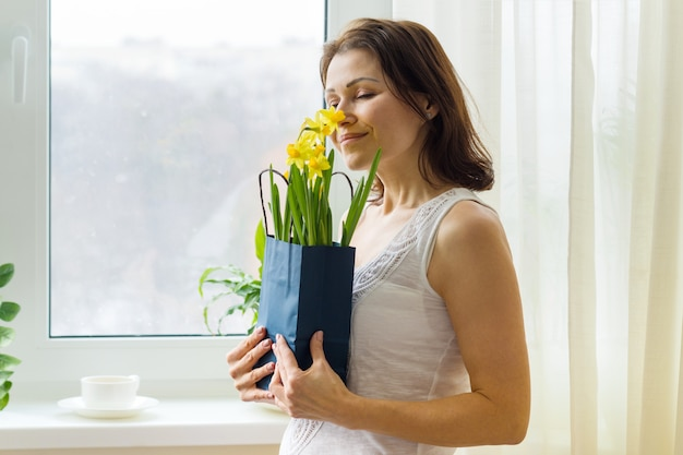 Middle aged woman enjoys bouquet of flowers