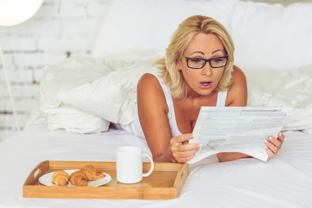 Middle aged woman in eyeglasses is reading a newspaper.
