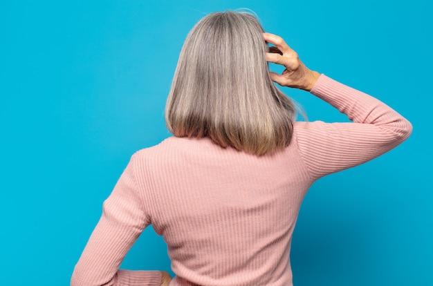 中年の女性は無知で混乱していると感じ、解決策を考え、腰に手を、頭に他の手を、背面図