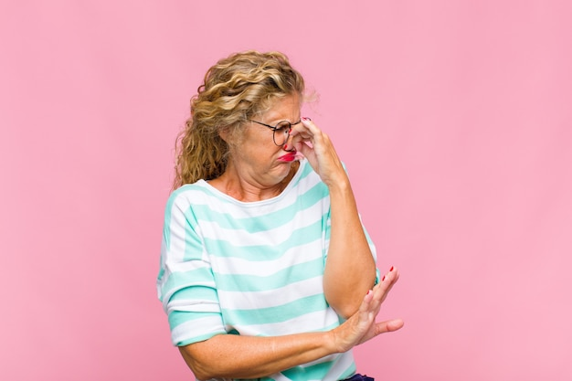 Middle aged woman feeling disgusted, holding nose to avoid smelling a foul and unpleasant stench