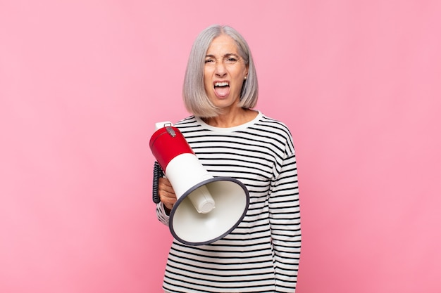 Middle aged woman feeling disgusted and irritated, sticking tongue out, disliking something nasty and yucky with a megaphone