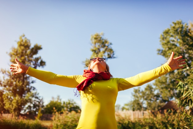 Middle aged woman feeling free and happy senior lady raising hands up