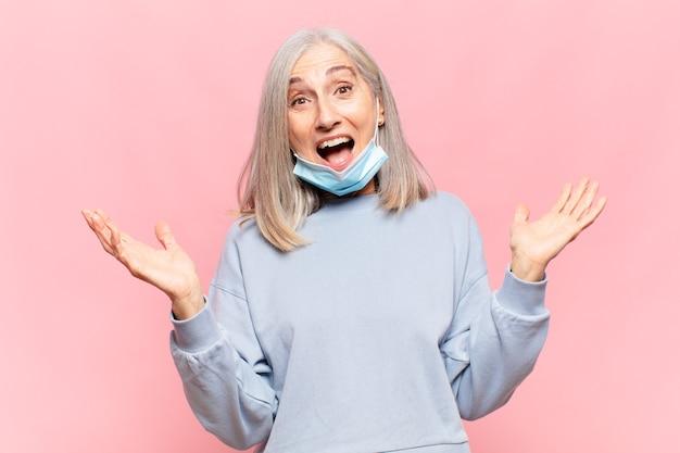 Женщина средних лет чувствует себя счастливой, взволнованной, удивленной или шокированной, улыбается и удивляется чему-то невероятному