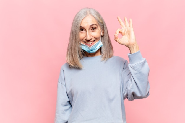 Middle aged woman feeling happy, relaxed and satisfied, showing approval with okay gesture, smiling