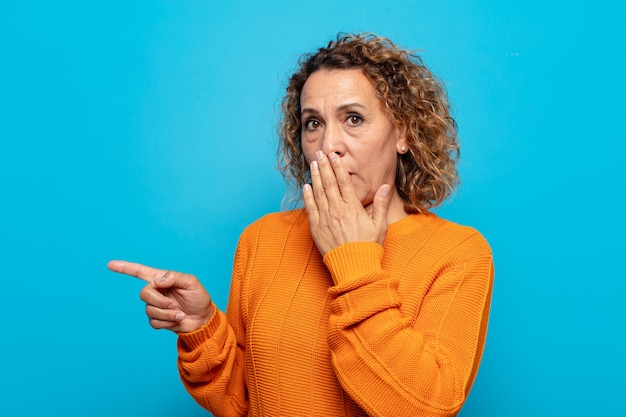 Middle aged woman feeling happy, shocked and surprised, covering mouth with hand and pointing to lateral copy space