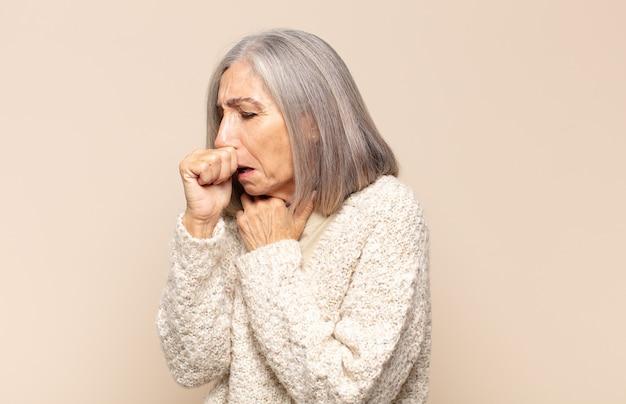 Женщина среднего возраста чувствует себя плохо, с симптомами гриппа и болью в горле, кашляет с прикрытым ртом