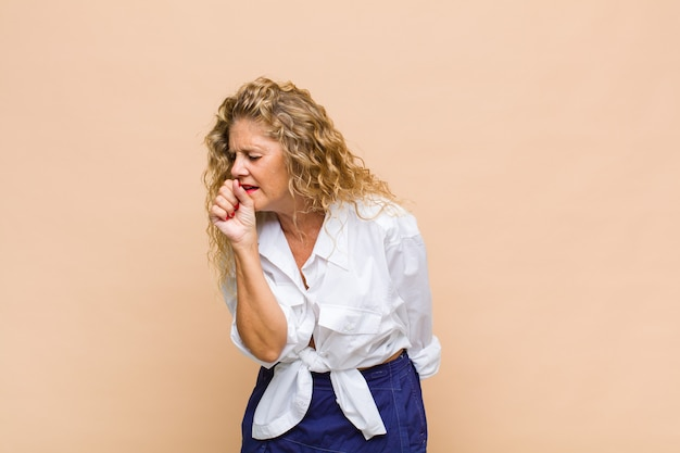 Middle aged woman feeling ill with a sore throat and flu symptoms, coughing with mouth covered