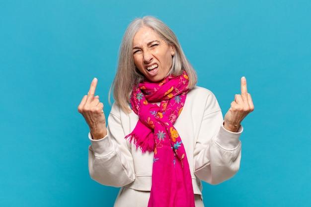 Женщина средних лет чувствует себя провокационно, агрессивно и непристойно, щелкая средним пальцем, с бунтарским настроем