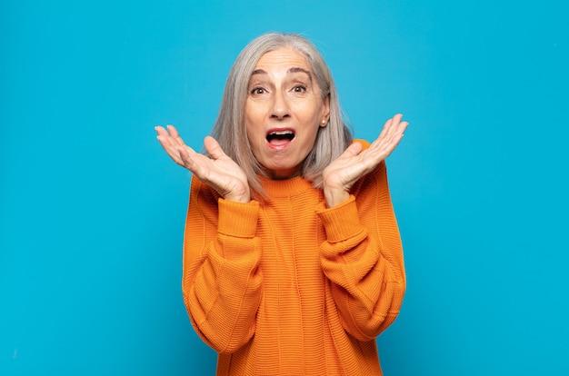 Женщина средних лет чувствует себя потрясенной и взволнованной, смеющейся, удивленной и счастливой из-за неожиданного сюрприза