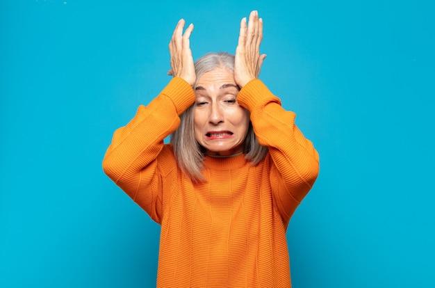 ストレスと不安を感じ、頭痛で落ち込んで欲求不満を感じ、両手を頭に上げている中年女性