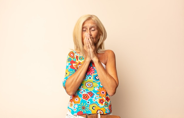 Женщина средних лет чувствует себя обеспокоенной, расстроенной и напуганной, прикрывает рот руками, выглядит встревоженной и испорченной