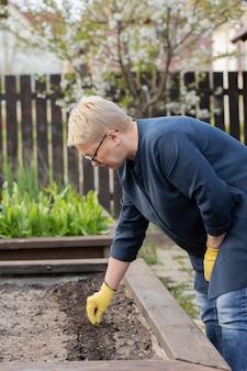 Женщина-садовник средних лет сажает семена в подготовленную рыхлую почву в своем саду.