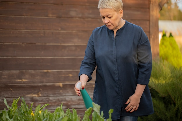 중년 여성 정원사는 분무기와 정원에서 식물을 스프레이
