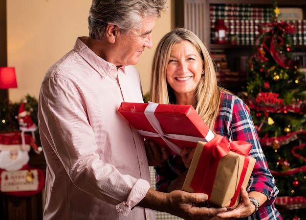 Средних лет женщина, давая подарок человеку,