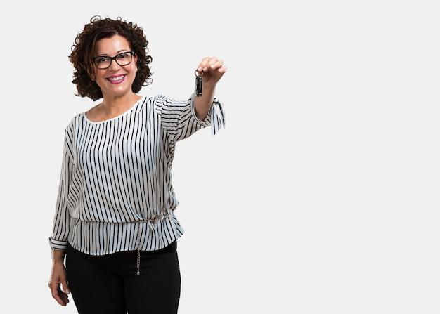 幸せと笑顔、自信を持って車のキーを保持している中年の女性